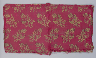 Gold floral forms in alternate diagonal directions on red. fragment pieced in center.