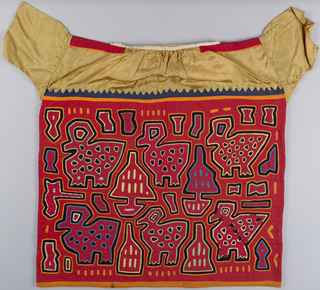 On a backing of black cotton, cut-out cottons with red predominating, outline large chunky bird with tree, and scattered angular shapes. This forms body of blouse and is sewn on to yoke of mustard-colored rayon.