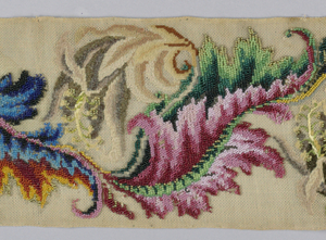 Pattern of repeated motif of curving flowers arranged to face alternately left and right.  Colors: several shades of blue, pink, green, brown, and gray.  Worked in beading, and tent and outline stitches.