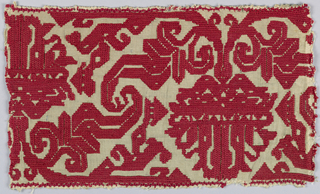 Pattern of curving plant and leaves in red silk on linen. Traces of overcastting and knotted decorative seam are at the top and bottom of the piece.