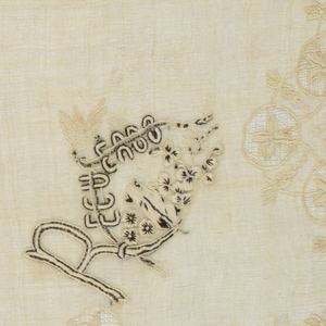 Handkerchief in piña cloth with scalloped edge, buttonholed and with border of flowering vine, embroidered in cotton, crossing circles of drawnwork. Corner in black and white with word: Recuerdos with bird above and small dog or cat below flowers.
