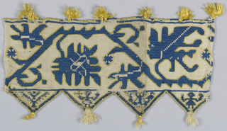 Band fragment with a tassled border showing a geometric vine in blue and yellow silk on a linen ground.