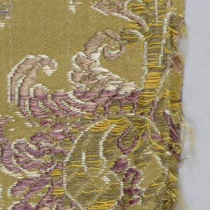Design of curving floral stem outlined in white on a mustard yellow satin ground.