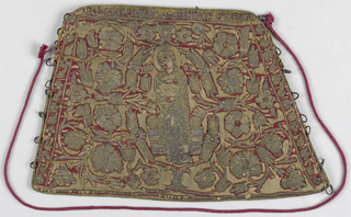 Cuff from garment of priest in Greek Orthodox Church. Red satin on linen ground, embroidered in silver. Figure of a woman (Mary) centre, surrounded by floral motifs. Fitted with rings at side and cord for lacing. Inscription.