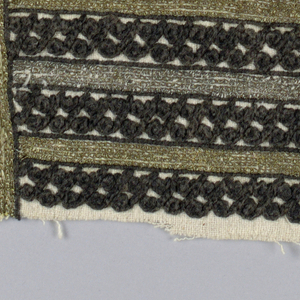 Portion cut from a sleeve of heavy white cotton. Bars of black cotton embroidery in simple repeat pattern are separated by rows of metallic embroidery in chain stitch.