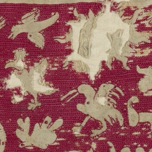 """Background embroidered in red silk; animals, etc. ornamented with red dots. Top border reads """"A Creation del Mundo --"""". At the left there is a narrow strip on white, the design is marked but not embroidered."""