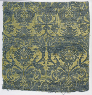 Fragment of woven silk with a symmetrical framework of scrolling leaves, confronted birds. In faded blue and gold.
