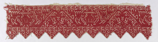 Border of natural linen with triangular tab edge, embroidered in red silk with a stylized floral vine growing out of an urn.