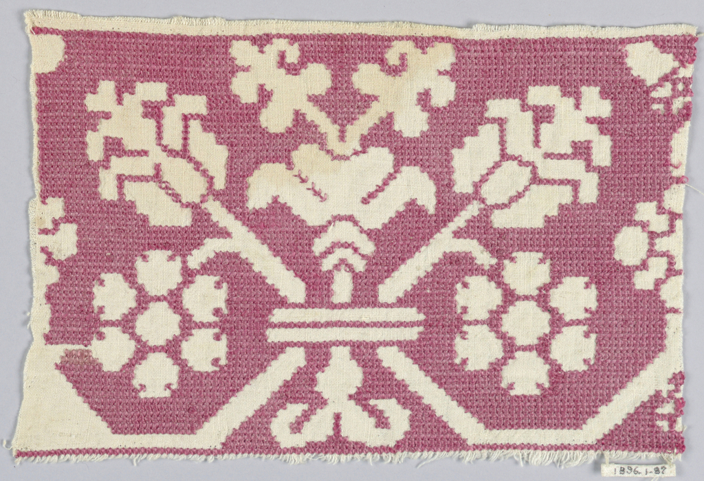 White linen foundation forms the design. Ground of drawn work embroidered with red silk. Symmetrical convetionalized floral groups, with one central branch and  two flanking branches.