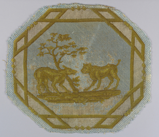 "Octagonal medallion of upholstery fabric illustrating a fable by Aesop known as ""The Fox and the Dog."" The pattern is in white and shades of yellow on a light blue ground."