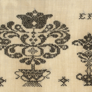 Motifs of flowering urns with a rooster in the middle with an elaborate border and corners.  All black on natural ground.