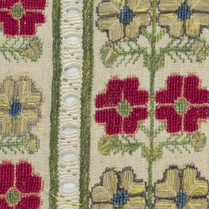 Three pieces of embroidered linen, with design arranged in narrow panels. Stylized flower heads on either side of straight vine, worked in red outlined in pink; in gold thread outlined in brown; and in green for stems. Panels separated by bands of white drawn work. Probably taken from trouser legs.