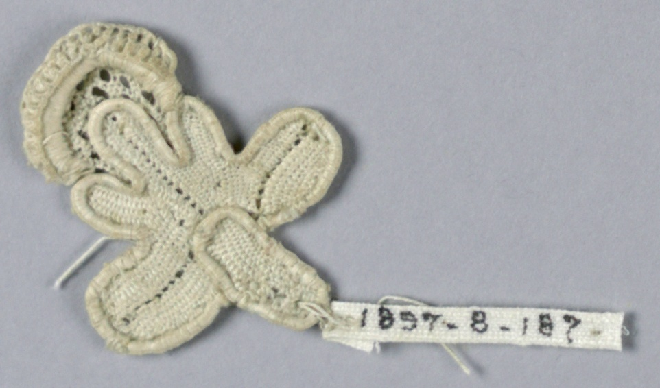 Fragment in a blossom and stem pattern with a trefoil in outline.