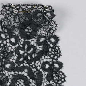 Cap fragment of black Honiton lace in a design showing the shamrock, rose and thistle for England, Ireland and Scotland.