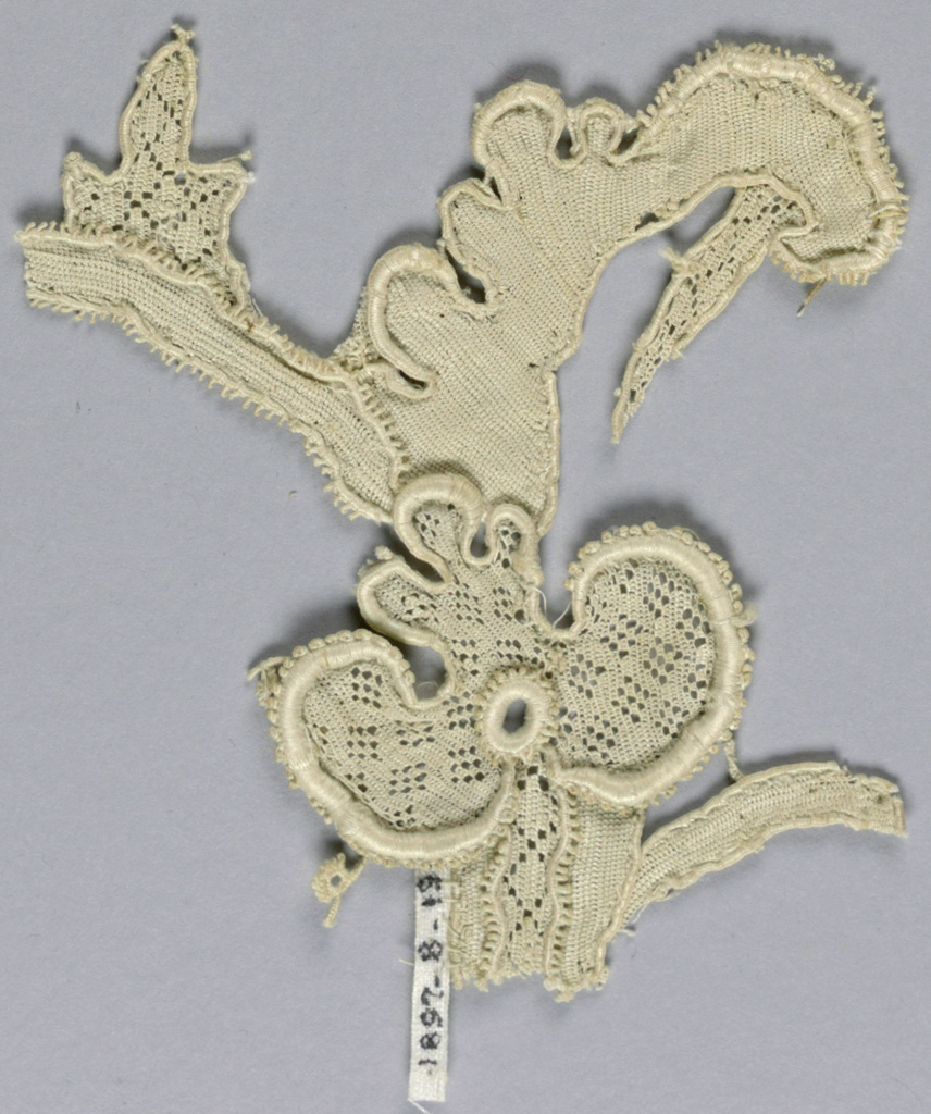 Fragment in a pattern of a trefoil blossom, large leaf and stem with small portions of surrounding design. Trefoil entirely lozenge diaper openwork. Leaf is scalloped.