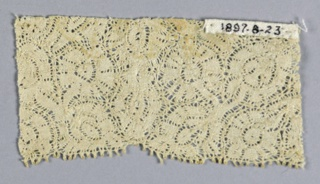 Closely spaced, tightly-worked design of a ribbon-like motifs. Slightly scalloped edge.