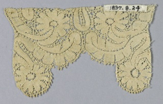 Closely-spaced, tightly worked design of ribbon-like flower and leaf motifs. Deeply scalloped edge.