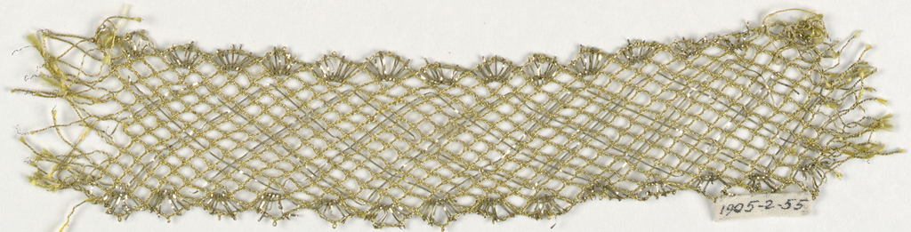 Gold color lace border in a design of diagonally-crossing lines with scallops on both edges. In yellow silk and metallic thread.