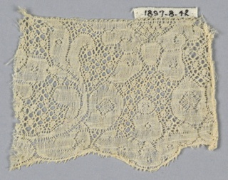 "Fragment of Binche lace with symmetrical floral design. ""Fond de neige"" ground."