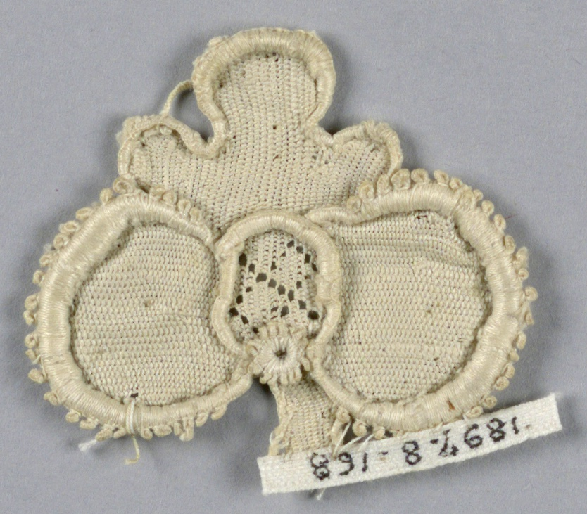 Fragment of raised lace in a pattern of trefoil blossom with a diamond diaper center and picot edge.