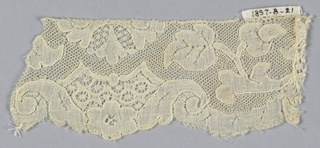 Scalloped border fragment with reserve areas of openwork along the edge. Floral spray design with heavy solid leaves.
