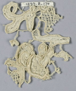Fragment of raised lace in a pattern of flower and leaves with small areas of surrounding design. Openwork and pin pricks. Flower has a picot edge.