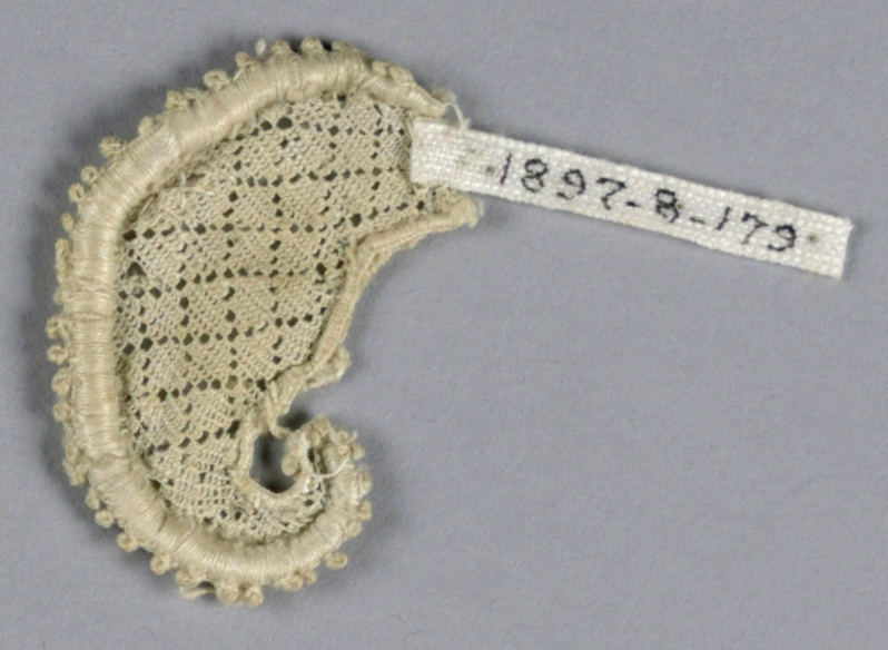 Fragment with a curving leaf motif in a diamond diaper pattern and picot edge.