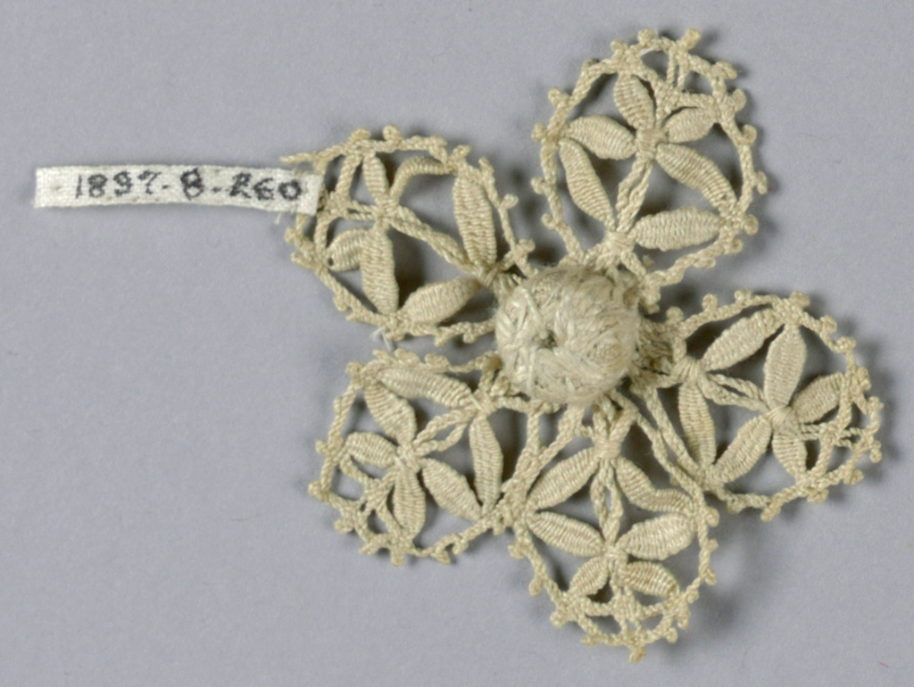 Fragment in a pattern of a small flower with several openwork petals.