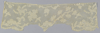 Border fragment with a scalloped edge and Valenciennes ground. Design of branches with flowers and fruit, curving to the right.