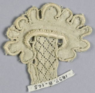 Fragment of raised lace in an ornamental flower design with a diamond diaper stem.