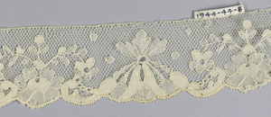 Chantilly-style lace with one scalloped edge formed by leaves and flowers.
