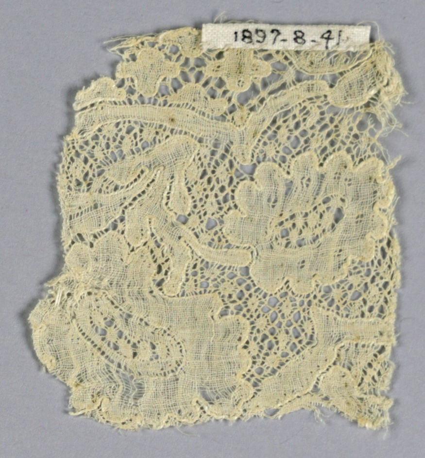 """Fragment of Mechlin lace with incomplete conventionalized design. """"Fond de neige"""" ground."""