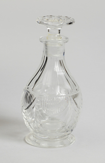 Pear-shaped body cut with drapery swags and flat vertical fluting; flat circular foot; mushroom-shaped stopper with radial cutting. One of set of seven bottles.