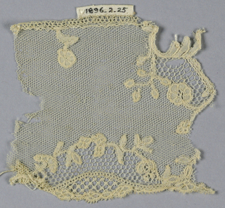 Brussels-style fragment showing reserve area on the border filled with bobbin imitation of needlepoint openwork stitches and set off by tiny floral wreath. Vrai droschel ground.