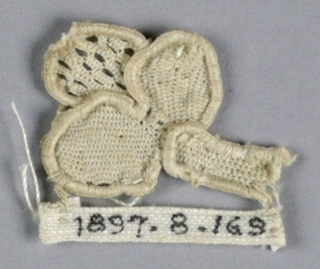 Fragment of raised lace with a tiny trefoil bud and open-work tip.