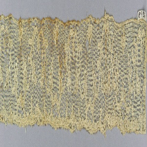 Border fragment of Lille-style lace with a serpentine conventionalized flowering vine design. Quatrefoils near top edge.