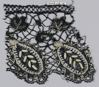 Cluny-type lace in a pattern of oval leaf forms and small flowers with connecting bars in black and white silk.