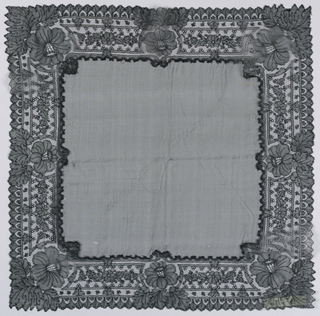 Black handkerchief with a sheer center center field and a deep border of black Chantilly-style lace. A large flower with leaves marks the four corners and the center of each side. Between are rows of scallops and small sprigs of flowers.