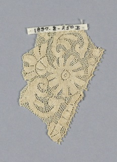 Fragments of closely-worked lace in a scroll and floral design.