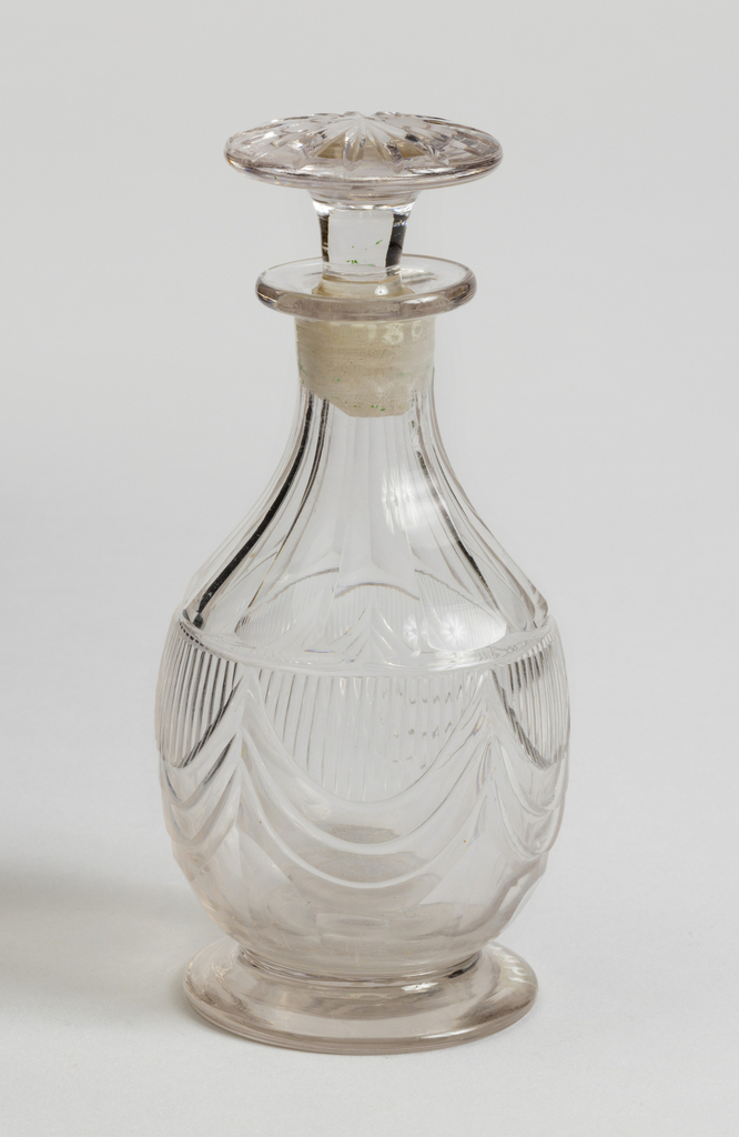 Pear-shaped body cut with drapery swags and flat vertical fluting; flat circular foot; mushroom-shaped stopper cut with radial grooves. One of setof seven bottles.