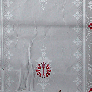 Medallion stripe design. Red and white medallions, alternating with smaller white motifs, repeating vertically. Vertical bands containing ornaments with red quatrefoils run between these vertical repeats. Printed in red and white on gray ground.