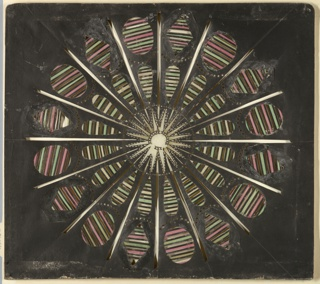 Magic lantern slide, optical toy. On black field, a sixteen-pointed star within a surrounding pierced circle at center. Outside circle, sixteen rays composed of tear-shaped openings filled with transverse stripes of yellow, green, and black, and of alternating ovals and lozenges similarly filled with stripes of pink, green, and black.