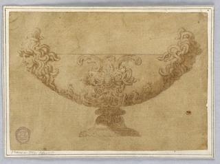 Elevation of a footed bowl with two gorgon heads. At center, a scrolling cartouche surrounding an oval. Shadow cast across the right lower half of the design.