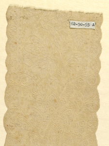 Cap streamers of Binche lace in a dense, symmetrical floral and foliated pattern. Surrounding compartments containing asymmetrical bouquets of carnations. Similar pattern, grounds are changed and shapes are different.