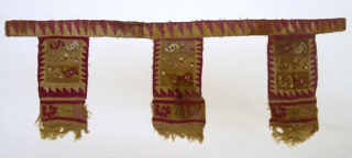 Tapestry woven strip patterned by stepped triangles in red and yellow to which three large tabs are attached (there might have been others). Each tab is made up of two sections sewn together: 1) rectangle patterned by three bands, with two bird heads (?) with tassels, bordered by stepped triangles in red and yellow 2) Natural orange plain weave wool embroidered with scroll bird-like motifs