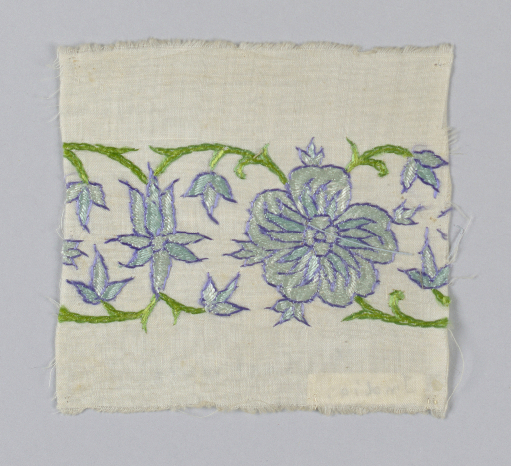 White muslin with band of embroidery in a  floral design of blue, green and purple.