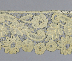 Duchesse-style lace with pattern of open flowers and leaves with côte and small scrolls.