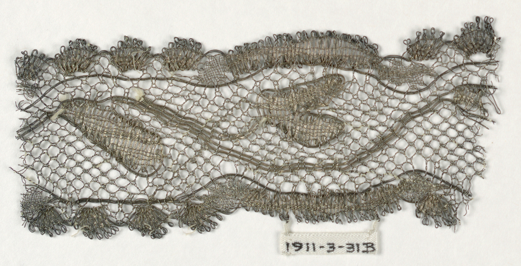 Fragment has a design of a curving stem with leaves and borders of large and small scallops in silver on white silk thread.