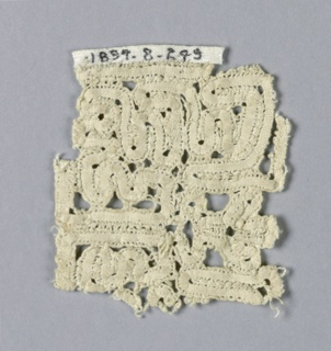 Fragment of a closely-worked, wavy, ribbon-like floral design.