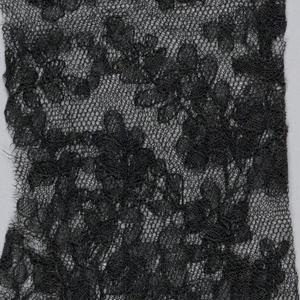 Pair of black mitts showing a flowering vine design.